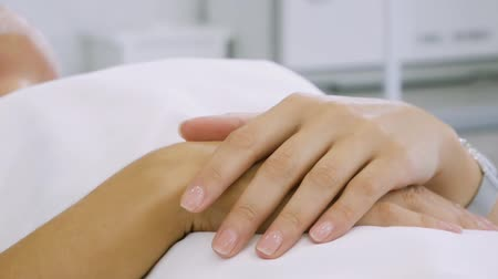 в ожидании : Female hands of a patient who lies on a medical couch in a beauty parlor. The concept of medical help. Rehabilitation and body care. Pending procedure Стоковые видеозаписи