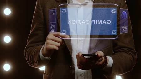estratégico : Businessman activates conceptual HUD hologram on smartphone with text Gamification. Man in a white shirt and jacket with a holographic screen on the background of lights