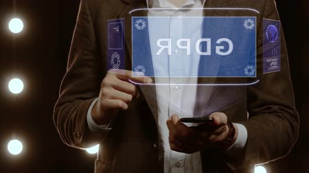 szabály : Businessman activates conceptual HUD hologram on smartphone with text GDPR. Man in a white shirt and jacket with a holographic screen on the background of lights