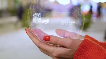 tir : Female hands holding a conceptual hologram with TIR Truck. Woman with red nails and sweater with future holographic technology on a blurred background of the street