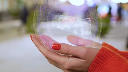 dvojitý : Female hands holding a conceptual hologram with two floored bus. Woman with red nails and sweater with future holographic technology on a blurred background of the street