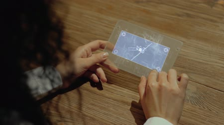 передавать : Unrecognizable woman working on a futuristic tablet with a hologram satellite. Womens hands with future holographic technology at a wooden table