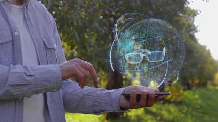 optical sight : Unrecognizable man shows conceptual hologram with eyeglasses. Farmer on the background of the apple orchard in casual clothes with the technology of the future mobile screen