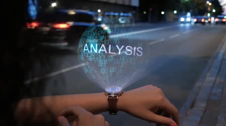 koncepció : Unrecognizable curly woman with a hologram on smart watch with text Analysis. Female hands with future holographic technology on the background of the night road
