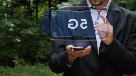 movilidad : Unrecognizable businessman activates conceptual HUD holograms on smartphone with text 5G. Bearded man in a white shirt and a jacket with a holographic screen on a background of green trees