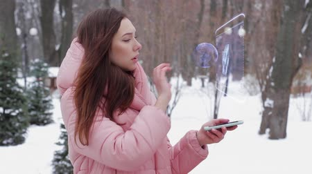 dvojitý : Beautiful young woman in a winter park interacts with HUD hologram with two floored bus. Red-haired girl in warm pink clothes uses the technology of the future mobile screen