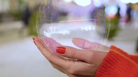 tir : Female hands holding a conceptual hologram with Americam Truck. Woman with red nails and sweater with future holographic technology on a blurred background of the street