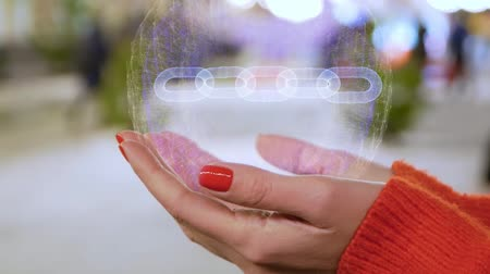 digital code : Female hands holding a conceptual hologram with particle chain. Woman with red nails and sweater with future holographic technology on a blurred background of the street
