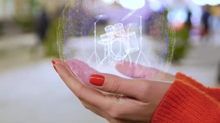 quadrilha : Female hands holding a conceptual hologram with drum set. Woman with red nails and sweater with future holographic technology on a blurred background of the street Stock Footage
