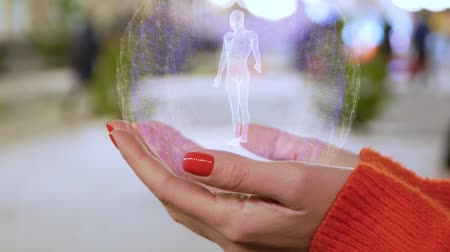 рентгеновский : Female hands holding a conceptual hologram with rotating man body particles. Woman with red nails and sweater with future holographic technology on a blurred background of the street