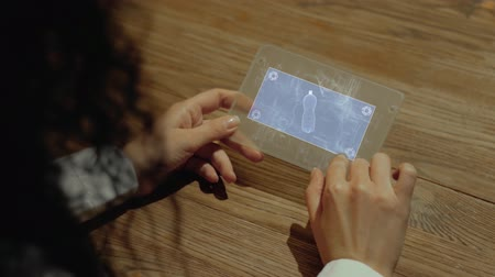 biodegradable : Unrecognizable woman working on a futuristic tablet with a hologram bottle. Womens hands with future holographic technology at a wooden table