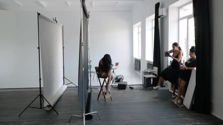 Studio photography. Female photographer in a black dress works with a model in a photo studio
