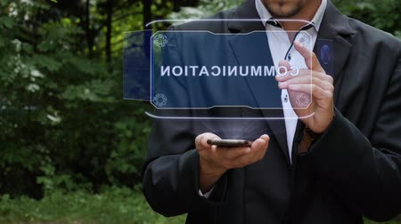 разведка : Unrecognizable businessman activates conceptual HUD holograms on smartphone with text Communication. Bearded man in a white shirt and a jacket with a holographic screen on a background of green trees Стоковые видеозаписи