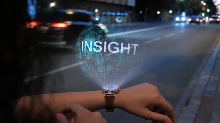 sabiduría : Unrecognizable curly woman with a hologram on smart watch with text Insight. Female hands with future holographic technology on the background of the night road