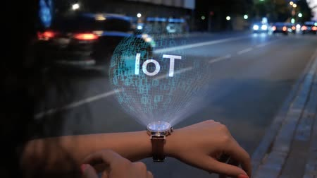 dolgok : Unrecognizable curly woman with a hologram on smart watch with text IoT. Female hands with future holographic technology on the background of the night road Stock mozgókép