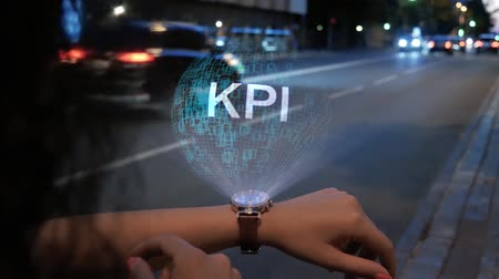 implementation : Unrecognizable curly woman with a hologram on smart watch with text KPI. Female hands with future holographic technology on the background of the night road