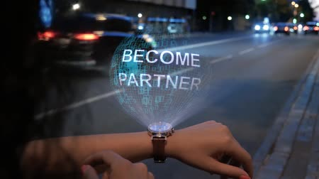 işbirliği yapmak : Unrecognizable curly woman with a hologram on smart watch with text Become partner. Female hands with future holographic technology on the background of the night road