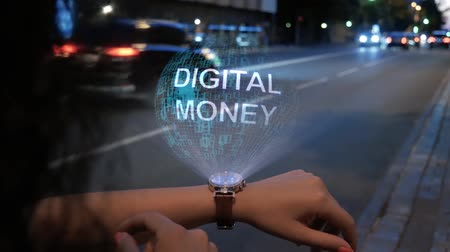 waluta : Unrecognizable curly woman with a hologram on smart watch with text Digital money. Female hands with future holographic technology on the background of the night road