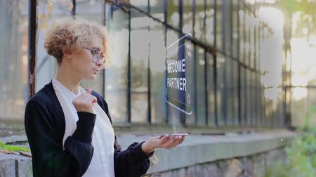 işbirliği yapmak : Curly young woman in glasses interacts with a hud hologram with text Become partner. Blonde girl in white and black clothes uses technology of the future mobile screen Stok Video