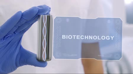 nanotechnologia : Hand in blue medical glove with a futuristic hud hologram with text Biotechnology. Medical concept of the technology of the future. Doctor with Futuristic Holographic Gadget Wideo