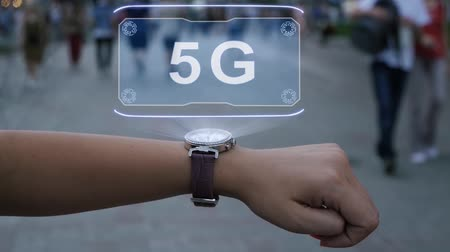 standardization : Female hand with futuristic smartwatch shows HUD hologram with text 5G. Woman uses holographic technology of future on wristwatch against background of evening city with people