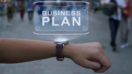 initiatief : Female hand with futuristic smartwatch shows HUD hologram with text Business plan. Woman uses holographic technology of future on wristwatch against background of evening city with people Stockvideo