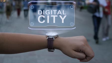 consumo : Female hand with futuristic smartwatch shows HUD hologram with text Digital city. Woman uses holographic technology of future on wristwatch against background of evening city with people