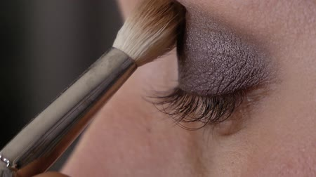 frustata : Professional makeup artist applies a brush to the upper eyelid of left eye beautiful girl with a brush. Client woman in beauty salon doing makeup close-up slowmotion Filmati Stock