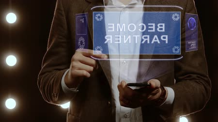 işbirliği yapmak : Businessman activates conceptual HUD hologram on smartphone with text Become partner. Man in a white shirt and jacket with a holographic screen on the background of lights Stok Video