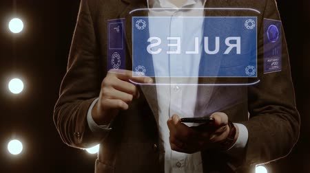 regulamin : Businessman activates conceptual HUD hologram on smartphone with text Rules. Man in a white shirt and jacket with a holographic screen on the background of lights