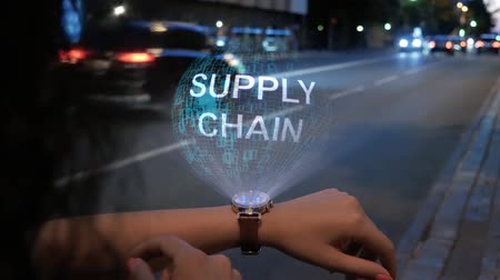 szállító : Unrecognizable curly woman with a hologram on smart watch with text Supply Chain. Female hands with future holographic technology on the background of the night road Stock mozgókép