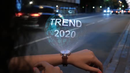 steigerung : Unrecognizable curly woman with a hologram on smart watch with text Trend 2020. Female hands with future holographic technology on the background of the night road Videos
