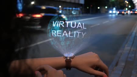 Unrecognizable curly woman with a hologram on smart watch with text Virtual Reality. Female hands with future holographic technology on the background of the night road
