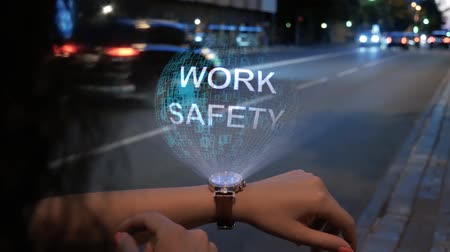 Unrecognizable curly woman with a hologram on smart watch with text Work safety. Female hands with future holographic technology on the background of the night road