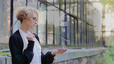 estratégico : Curly young woman in glasses interacts with a hud hologram with text Business plan. Blonde girl in white and black clothes uses technology of the future mobile screen