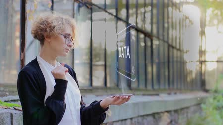 Curly young woman in glasses interacts with a hud hologram with text Data. Blonde girl in white and black clothes uses technology of the future mobile screen