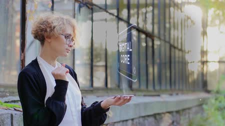 mededeling : Curly young woman in glasses interacts with a hud hologram with text Digital Core. Blonde girl in white and black clothes uses technology of the future mobile screen