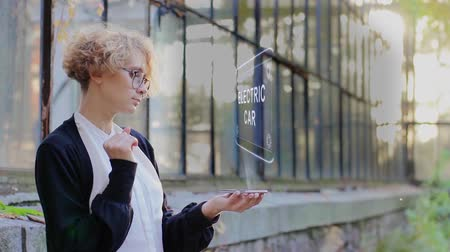 Curly young woman in glasses interacts with a hud hologram with text electric car. Blonde girl in white and black clothes uses technology of the future mobile screen