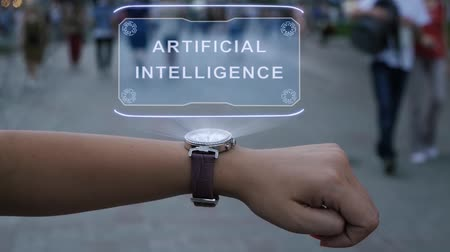 este : Female hand with futuristic smartwatch shows HUD hologram with text Artificial Intelligence. Woman uses holographic technology of future on wristwatch against background of evening city with people