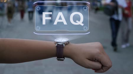 Female hand with futuristic smartwatch shows HUD hologram with text FAQ. Woman uses holographic technology of future on wristwatch against background of evening city with people