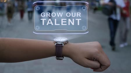 oluşturmak : Female hand with futuristic smartwatch shows HUD hologram with text Grow our talent. Woman uses holographic technology of future on wristwatch against background of evening city with people