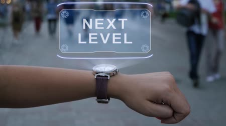 klatka schodowa : Female hand with futuristic smartwatch shows HUD hologram with text Next level. Woman uses holographic technology of future on wristwatch against background of evening city with people Wideo