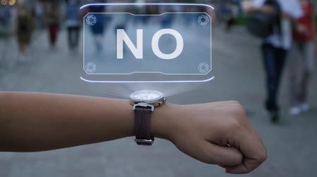 city limits : Female hand with futuristic smartwatch shows HUD hologram with text No. Woman uses holographic technology of future on wristwatch against background of evening city with people