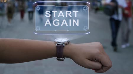 Female hand with futuristic smartwatch shows HUD hologram with text Start Again. Woman uses holographic technology of future on wristwatch against background of evening city with people
