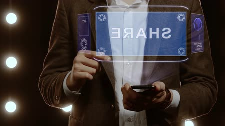 következik : Businessman activates conceptual HUD hologram on smartphone with text Share. Man in a white shirt and jacket with a holographic screen on the background of lights