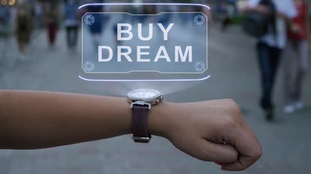 waluta : Female hand with futuristic smartwatch shows HUD hologram with text Buy dream. Woman uses holographic technology of future on wristwatch against background of evening city with people