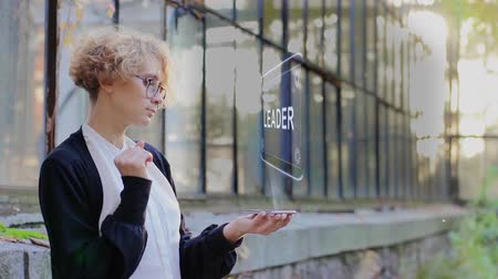 promover : Curly young woman in glasses interacts with a hud hologram with text Leader. Blonde girl in white and black clothes uses technology of the future mobile screen Stock Footage