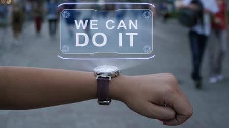 faca : Female hand with futuristic smartwatch shows HUD hologram with text We can do it. Woman uses holographic technology of future on wristwatch against background of evening city with people