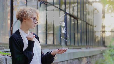 waluta : Curly young woman in glasses interacts with a hud hologram with text Buy time. Blonde girl in white and black clothes uses technology of the future mobile screen Wideo
