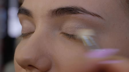 contorno : Hand of a professional makeup artist applies a brush to the upper eyelid of a beautiful girl with a brush. Close-up in beauty salon. Client woman in beauty salon doing makeup Stock Footage